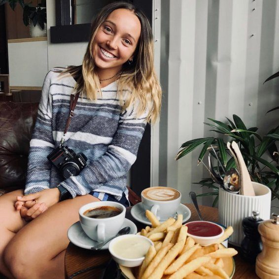 Photo of Lane, smiling at a table with coffee and french fries