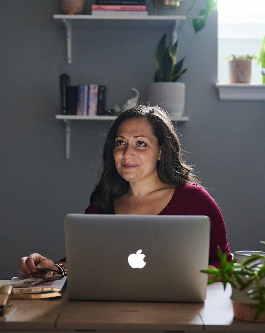 Nina sitting at her desk on her computer